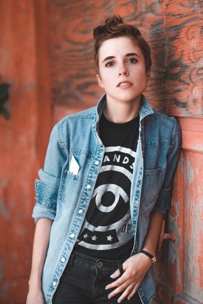 Short haired person in jean jacket leaning against wall