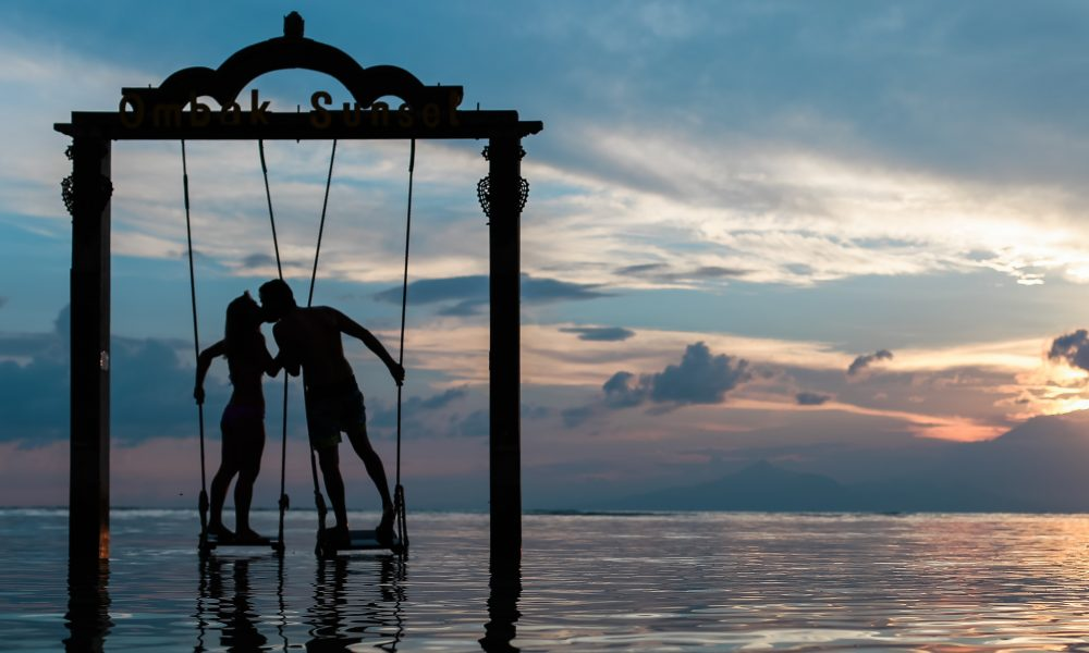 Couple standing on swings and kissing in the water