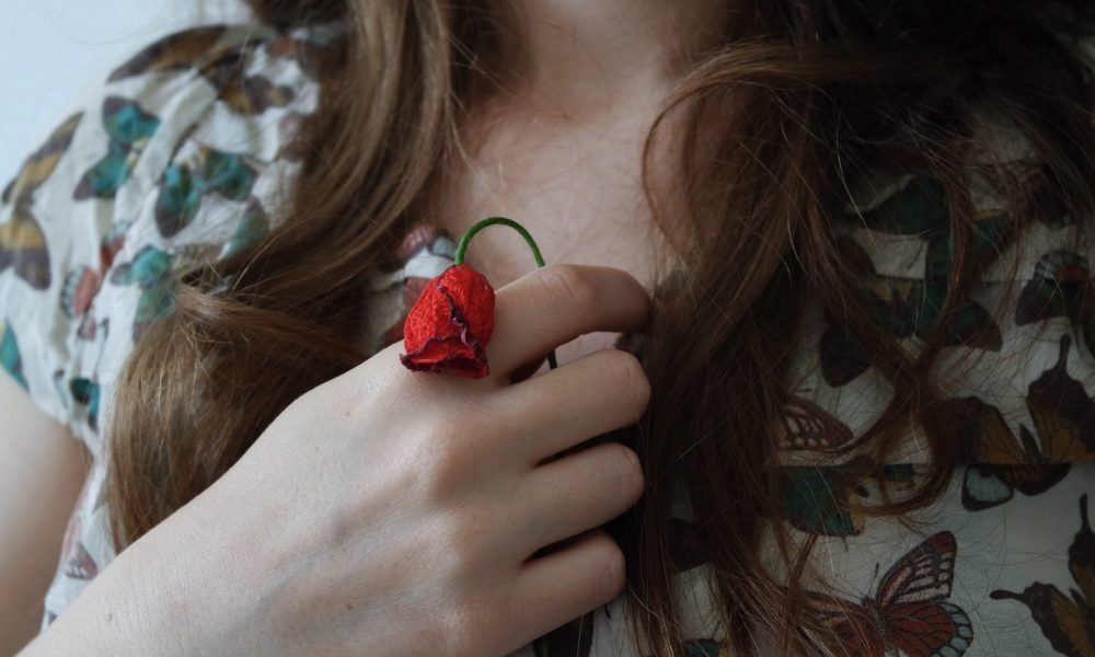 Image shows a woman holding a wilted rose, representing erectile challenge or erectile dyfunction