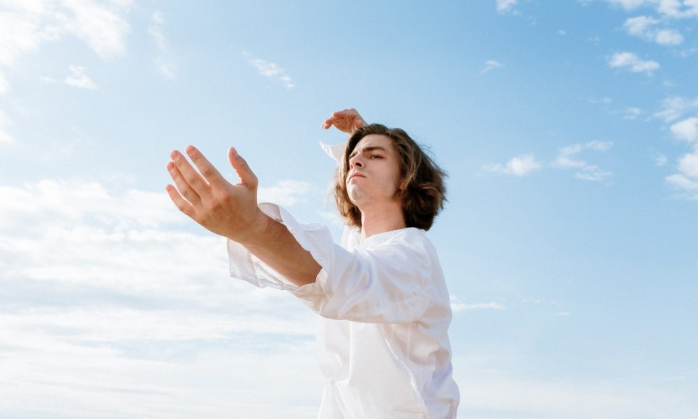 a man dancing with a blue sky behind him because he learned how to last longer in bed