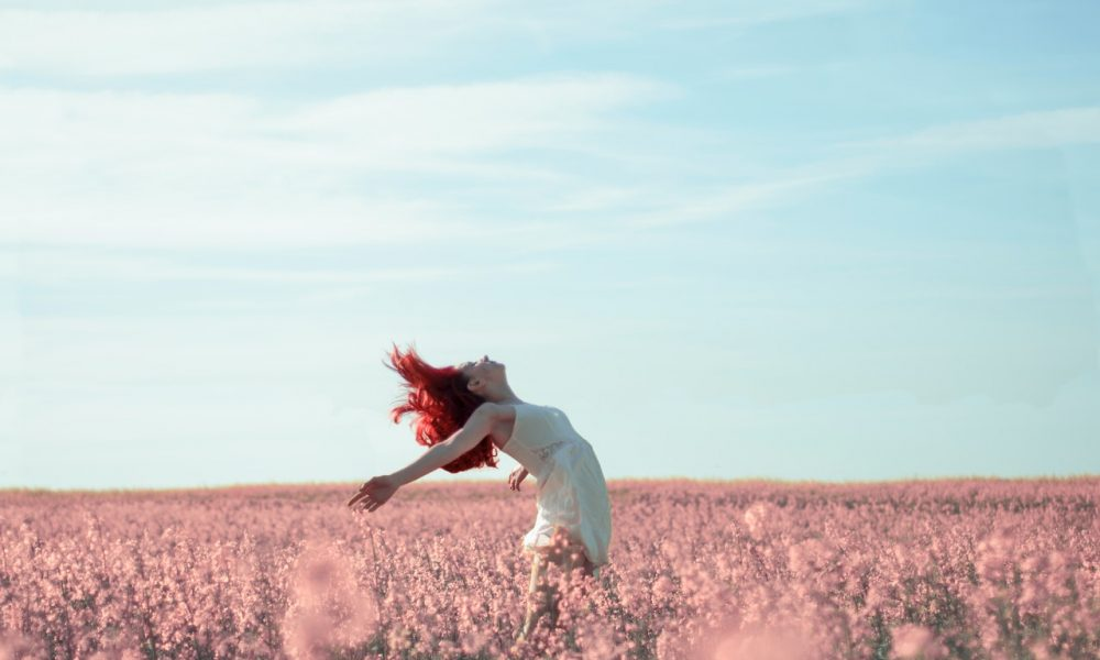 a woman in a field carefree and living orgasmically