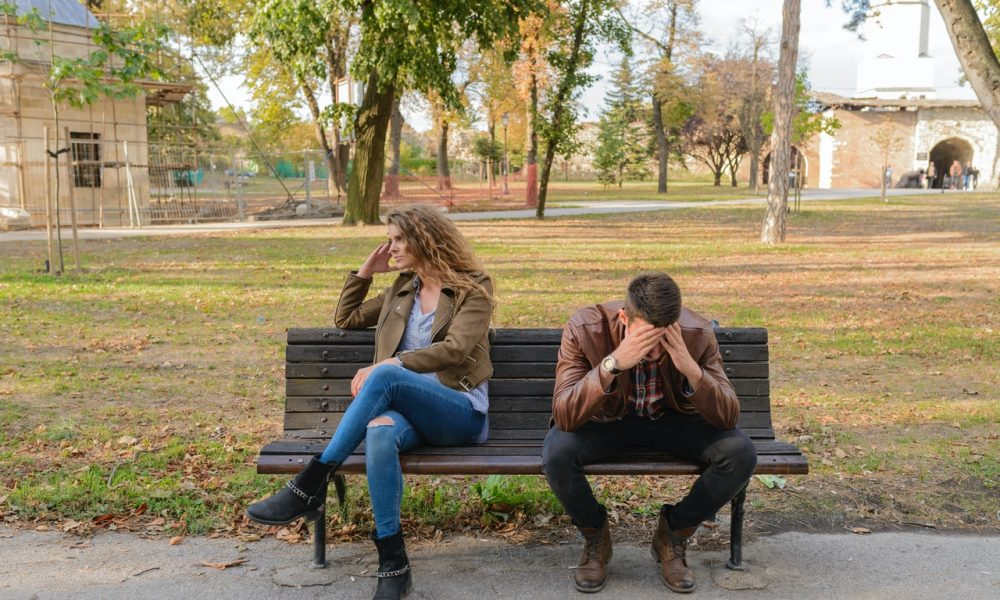 a couple in a sexless marriage sits on a bench