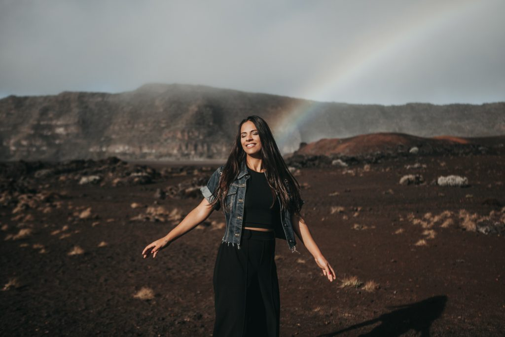 Woman with eyes closed and wearing denim jacket stands in front of dark mountain with a rainbow ending behind her head.