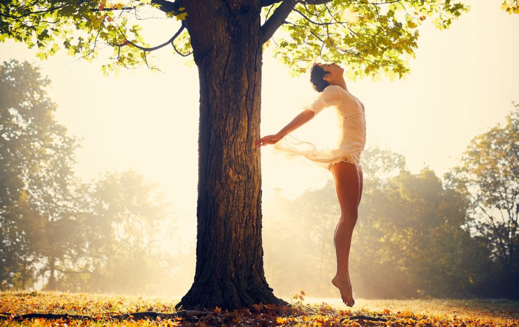 Person in wispy dress leaps into air beside tree with sun shining brightly behind them.