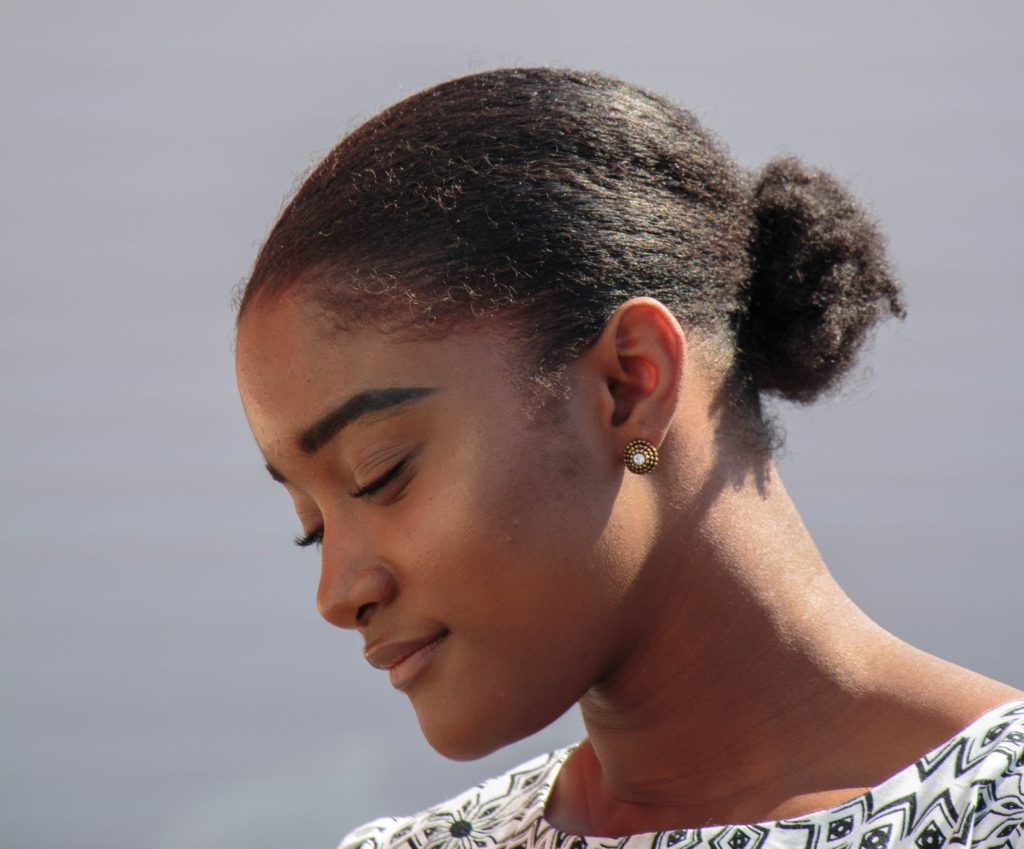 Profile of woman with black hair in a bun, looking down with a slight smile