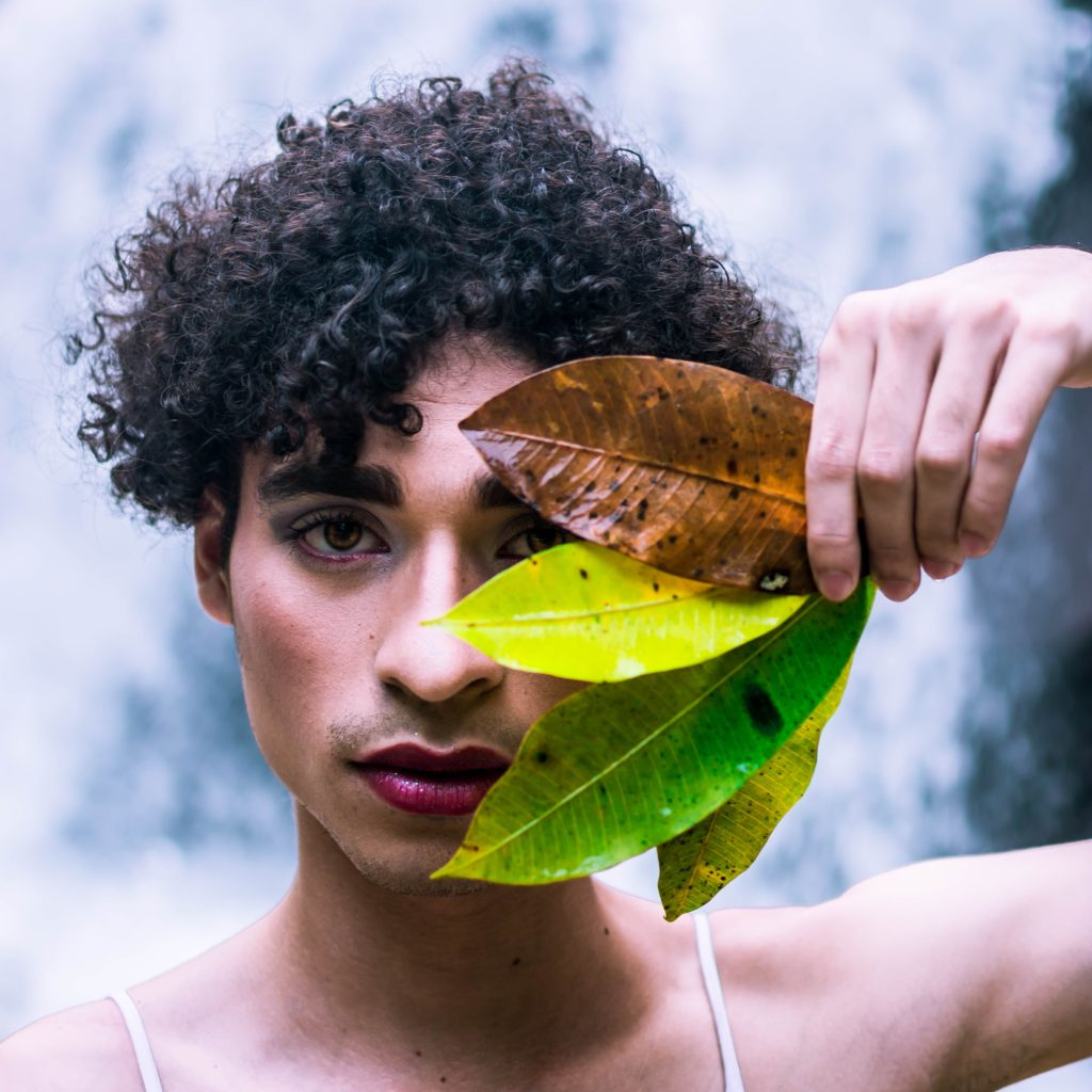 Person with curly hair holding autumn leaves obscuring one side of face