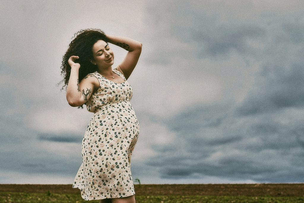 Adult in flowered dress with tattoos walking with eyes closed and hands in long hair