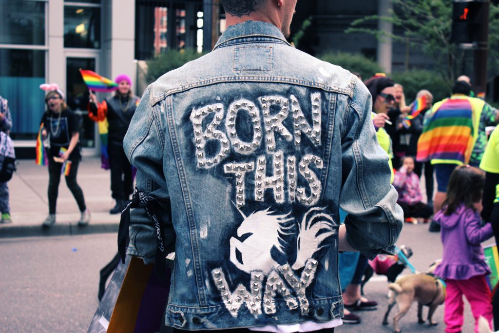 "Person facing away from camera wearing jean jacket that says ""Born This Way"""